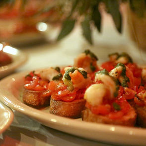 """""""Shrimp Toast,"""" with a grilled shrimp and roasted heirloom tomato over a toasted French bread slice, comes with a drizzle of pesto over the top. Michael likens a stuffed baked bread on the offerings to a stromboli or empanada. His version is called """"Impanata."""""""