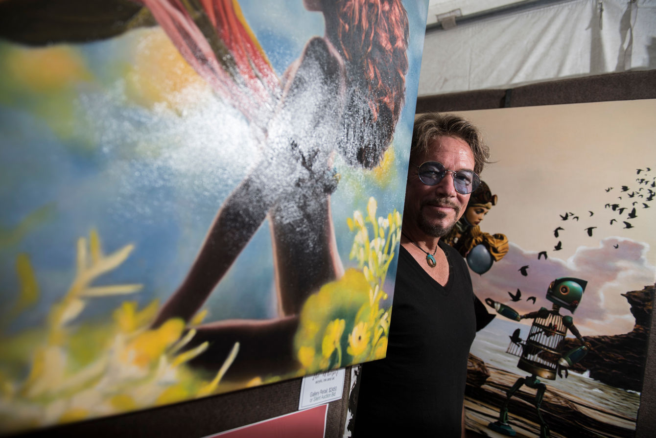 "<p>Vic Lee, a painter from St. Johns, Florida, stands among his paintings during the second day of the annual Ann Arbor Art Fair on Friday, July 20, 2018. Lee said he draws artistic inspiration from the prevalence of mythology in organized religion. ""Every bit of our traditions originate somewhere,"" he said. ""We're always asking questions and if the answers don't satisfy, people take things on faith."" All proceeds from sales of his paintings will go towards preventing shelter dogs from being euthanized, he said. (Ben Allan Smith/MLive.com)</p>"
