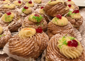 Zeppole are sliced in half and filled with custard cream, then topped off pistachio and cherries.