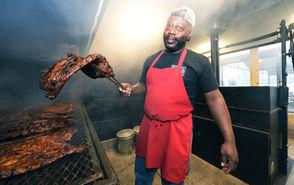 Rodney Scott, a James Beard Award-winning chef, tends to a batch of pork ribs in the Pit Room. (Joe Songer | jsonger@al.com).