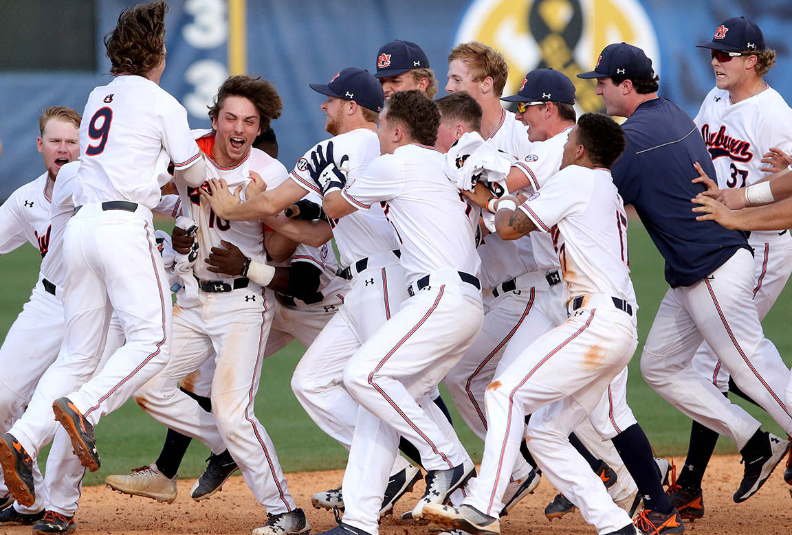 Auburn players mob Edouard Julien after his game-winning hit against Kentucky during the SEC baseball tournament at the Hoover Met in Hoover, Ala., Tuesday, May 22, 2018. (Dennis Victory/preps@al.com)