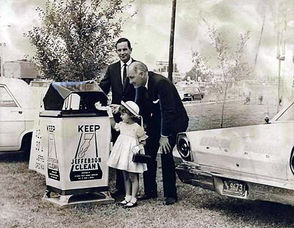 """Jodie Ann Taravella deposits the first scrap paper into the """"Keep Jefferson Clean"""" receptacle at the Marrero Water Plant to open an anti-litter campaign in the parish. Standing by during the ceremonies are Ross Ketchum, left, representing Parish President Thomas F. Donelon, and Sheriff Alwynn J. Cronvich. 1967 photo."""
