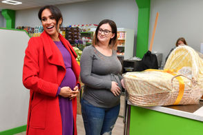 Britain's Meghan, Duchess of Sussex, left, presents Angela Midgley with a baby basket as she and Prince Harry officially open Number 7, a 'Feeding Birkenhead' citizens supermarket and community cafe, at Pyramids Shopping Centre, as part of a visit to Birkenhead, northwest England, Monday Jan. 14, 2019.