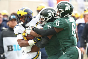 Michigan State linebacker Andrew Dowell (5) and safety David Dowell (6) tackle Michigan running back Chris Evans (12) during the first quarter of their Big Ten football game at Spartan Stadium in East Lansing on Saturday, October 20, 2018. (Mike Mulholland | MLive.com) Mike Mulholland | MLive.com