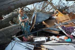 (Kathy Coy stands among what is left of her home after Hurricane Michael destroyed it on October 11, 2018 in Panama City, Florida. She said she was in the home when it was blown apart and is thankful to be alive. The hurricane hit the Florida Panhandle as a category 4 storm. (Photo by Joe Raedle/Getty Images)