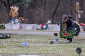 Kyla Nicholson, 15, of Vandercook Lakelays a wreath at the grave of Frank Jabkiewicz, a World War II U.S. Army veteran, Saturday, Dec. 15, 2018 at St. John Cemetery in Jackson. (Nikos Frazier | MLive.com)