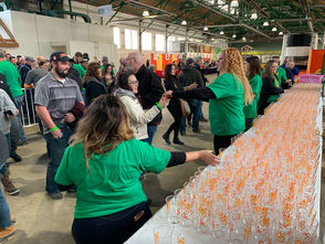 Volunteers distribute tasting glasses to attendees at the 2019 CNY Brewfest at New York State Fairgrounds' Horticulture Building on February 2.