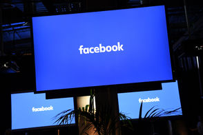 """A Facebook logo is pictured on a screen ahead of a press conference to announce the launch of it's latest product """"Workplace"""", in central London on October 10, 2016."""