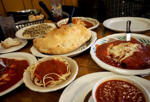 There's a colorful trend in most of the food in Angotti's, in case you couldn't tell by the picture above. The red sauce is a family recipe owners Bobby Angotti and his parents Anthony and Susie developed when they took over the restaurant in 1986 from Carmine Angotti, Bobby's grandfather, who opened the restaurant in 1961, five years after he moved from Taverna, Italy to Syracuse. Related: Keeping it classic: 4 Syracuse Italian restaurants that have stood the test of time The sauce coats the bottoms of platters of chicken Parmesan, lasagna and eggplant Parmesan like a silky-smooth bedsheet. It tops the side bowls of al dente spaghetti. When our waitress asked if we'd like a side of sauce for our hilariously-large cheese and sausage calzone, we said yes, not knowing that it was akin to bringing a kiddie pool to the ocean. Clockwise from bottom left: Eggplant Parmesan ($14.95), linguini with white clam sauce ($11.95), lasagna ($8.95), chicken Parmesan ($14.95), cup of extra sauce, side of spaghetti and a sausage and cheese calzone ($7.25).