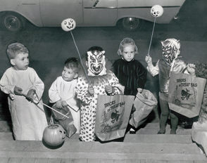 Miniature ghosts and goblins haunt a doorstep in New Orleans on Oct. 31, 1961, seeking a Halloween treat. From left are Russell and Robert Dearie, dressed as spooky ghosts; Mark Hunter, making his rounds in the somewhat unusual combination of a clown suit and a devil mask; Donna Dearie, minus her witch's mask in hopes of getting a treat; and Susan Hunter, grinning ferociously from behind her red devil mask.