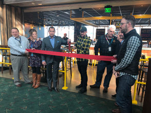 Christian Ettinger (center in cap), the founder and brewmaster at Hopworks, cuts the ribbon Wednesday morning with airport, food service and Port of Portland officials as well as brewery partners at the opening of the brewery's new pub at PDX.