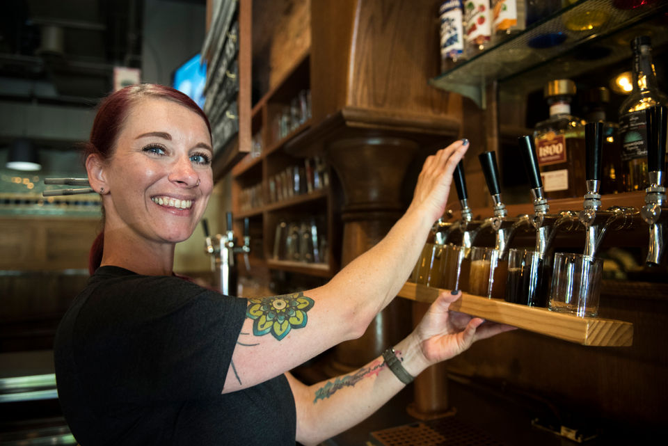 """Amber Dulimba, a bartender at Grizzly Peak, poses for a portrait at Grizzly Peak on Wednesday, July 11, 2018. Grizzly Peak is one of many Ann Arbor restaurants dealing with industry labor shortages. Dulimba mentioned pay and benefits are essential to any good restaurant job. """"They have to give incentives like for any career,"""" she said. (Ben Allan Smith 