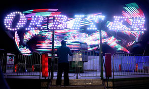 As the sun gets lower in the horizon the New York State Fair's midway takes on a different look. The skies take on an amber look, the shadows grow longer and neon lights of the rides burst with bright colors in motion.