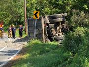 Truck rolls onto side, dumps load of gravel (PHOTOS)