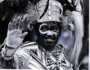 """The 1971 King of Zulu, Anthony J. """"Chuck"""" Mercadel, beams to the masses of parade followers as he makes a brief stop at Gallier Hall on his way down St. Charles Avenue. The theme of Zulu's parade that year was """"Zulu Sports Page."""""""