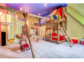 Vaulted indoor playroom with a swing-set play structure: The 1911 Bishopcroft mansion at 1832 SW Elm St. in Portland, which is listed at $2.5 million, has an art studio, media room, entertainment arena with a home theater, game room and a former ballroom that's now a vaulted indoor playroom with a swing-set play structure. The English Tudor-style house, designed by David C. Lewis and built in 1911 on a 10,018-square-foot lot, has five bedrooms, 5.5 bathrooms and 8,888 square feet of living space ($281 a square foot), say listing agents Marcia Kies and Rebecca Green of Hasson Company