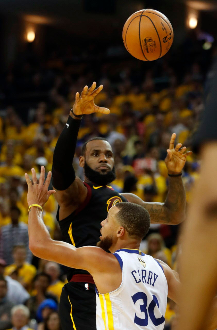 37a9cae52877 Cleveland Cavaliers forward LeBron James passes over Golden State Warriors  guard Stephen Curry in the second