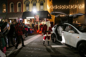 Santa Claus pauses for Mrs. Claus as they emerge from their sleigh, a Tesla Model X, during the annual Depot Town Christmas tree lighting, Sunday, Nov. 18, 2018 in Ypsilanti. (Nikos Frazier | MLive.com)