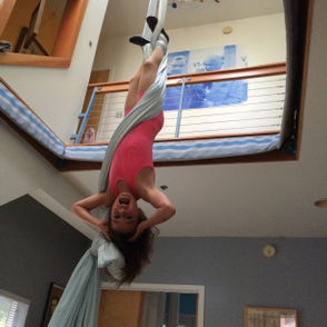 For experienced aerial dancers, at ease being aloft, the net doubles the landing arena, reducing crowding on the floor below. (This photo shows Kris Homsi's daughter doing a double ankle hang.)